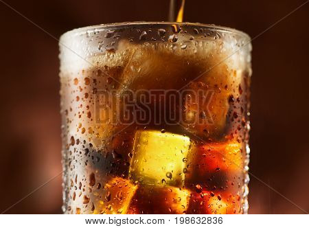 Pouring Cola with ice cubes
