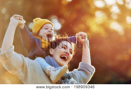 poster of Happy family on autumn walk! Mother and daughter walking in the Park and enjoying the beautiful autu
