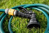 Garden hose head in a coil of hose, on green grass.