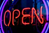 Blue, purple and red neon sign of the word 'Open' inside two rings of lighting, on a black backgroun