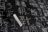 Chalk on blackboard filled with Chinese and Japanese characters. The words in Japanese have random m