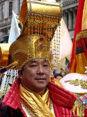 Chinese man in costume with golden headdress at New Year celerations
