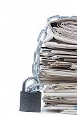 pile of newspapers with chains on white