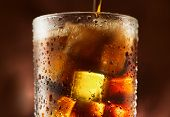 Pouring Cola with ice cubes. Cola drink with Ice and bubbles. Water drops on glass. Soda closeup. Br poster