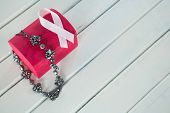 High angle view of jewelry with red box and pink Breast Cancer Awareness ribbon on wooden table poster