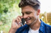 Smiling man talking on mobile phone in garden on a sunny day poster