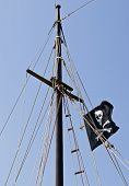 stock photo of pirate flag  - Pirate flag on the sailboat waving in the wind - JPG