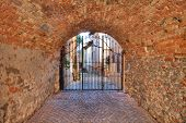 Old brick arched passage leading towards metal gate at the entrance to courtyard in La Morra, Italy.