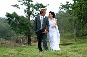Bride And Groom Walking Hand In Hand In Rural Setting