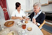 picture of geriatric  - a geriatric nurse helps elderly woman at breakfast - JPG