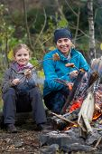 Campfire - Mother and daughter are baking sausages at the bonfire