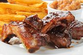 stock photo of baby back ribs  - Close up of beef or pork ribs with fries and baked beans - JPG