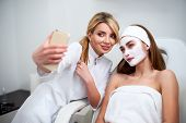 Beautician Blogger Making Selfie With Client After Applying Facial Mask For Healthy Skin. Attractive poster