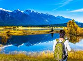 Shores of Abraham Lake in the Rocky Mountains. Canada. Middle-aged woman with a large green tourist  poster
