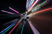View from side of car moving in a modern night city, blurred motion with lights and cars. poster