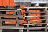 Stacks Of Colorful Rough Wooden Pallets At Warehouse In Industrial Yard. Pallets On Orange Backgroun poster