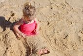 Little girl sits buried in the sand
