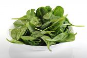 Bowl overfilled with spinach with white background
