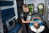 stock photo of triage  - Female EMT worker tending to ill senior patient - JPG