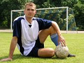 Soccer Player Sitting On A Field In Front Of A Goal Net