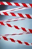 Fita de barreira plástica vermelha e branca bloqueando o caminho.