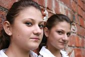 foto of fraternal twins  - Similar sisters looking at you and smiling - JPG