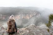 Female Dressed In Warm Winter Attire Sitting On The Cliff Ledge Looking Out Into The Misty Fog Fille poster
