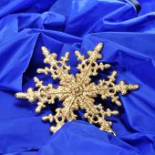 a golden christmas ornament with the shape of a snowflake on a blue fabric background