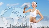 Young pretty woman in sport wear holding a bottle with pure water