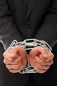 Close up of businessman hands chained over a white background