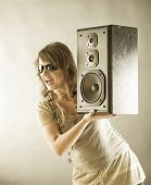 Young beautiful smiling woman with sunglasses holding big wooden speaker and listening music