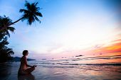 Beautiful woman doing lotus yoga pose on the beach near the ocean at sunset in Thailand