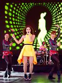 Beautiful woman singing in front of large LED screen