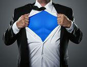stock photo of superman  - Young businessman acting like a super hero and tearing his shirt off with copy space - JPG