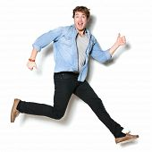 Jumping man happy excited. Funny portrait on young casual male male model in humorous jump on white