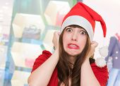 image of horrifying  - scared woman wearing a christmas hat in front of a shop - JPG