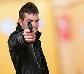 man with leather jacket pointing with gun against an abstract background