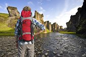 Hiker with a backpack admiring the trail throug an ancient Canyon in Hunkarbakkar, Iceland, where th