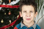 stock photo of pain-tree  - Unhappy little boy on christmass - JPG