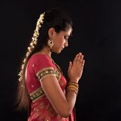 Portrait of beautiful young Indian woman prayer in traditional sari dress, isolated on black background.