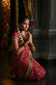 Young Indian woman in traditional sari dress praying in a hindu temple.