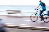 Great way to get around in a city -Motion blurred cyclist going fast on a city bike lane, by the sea