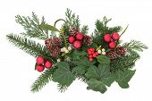 Christmas floral arrangement with red baubles, holly, ivy, mistletoe, pine cones and winter greenery over white background.