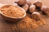 stock photo of ground nut  - Ground nutmeg spice in the wooden spoon closeup - JPG