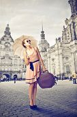 beautiful tourist with umbrella and old suitcase around the city