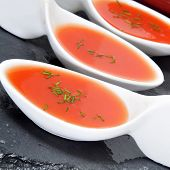 some little bowls with spanish gazpacho served as tapas on a slate background