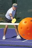 pic of pickleball  - Sports action image of senior man completing a backhand stroke during a pickleball match - JPG
