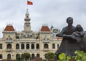 Ho Chi Minh Statue And Saigon City Hall With Flag.