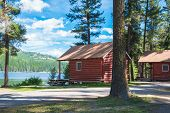 pic of bonaparte  - Two red log cabins at a resort sit in the forest on a lake - JPG