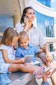 Busy mother with mobile phone, kids sit with electronic tablet